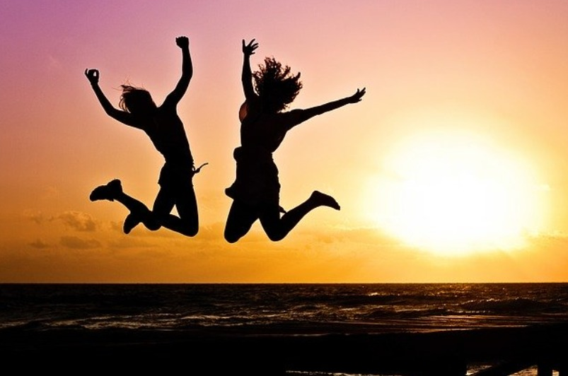 happy-jump-ocean-dark-sunset